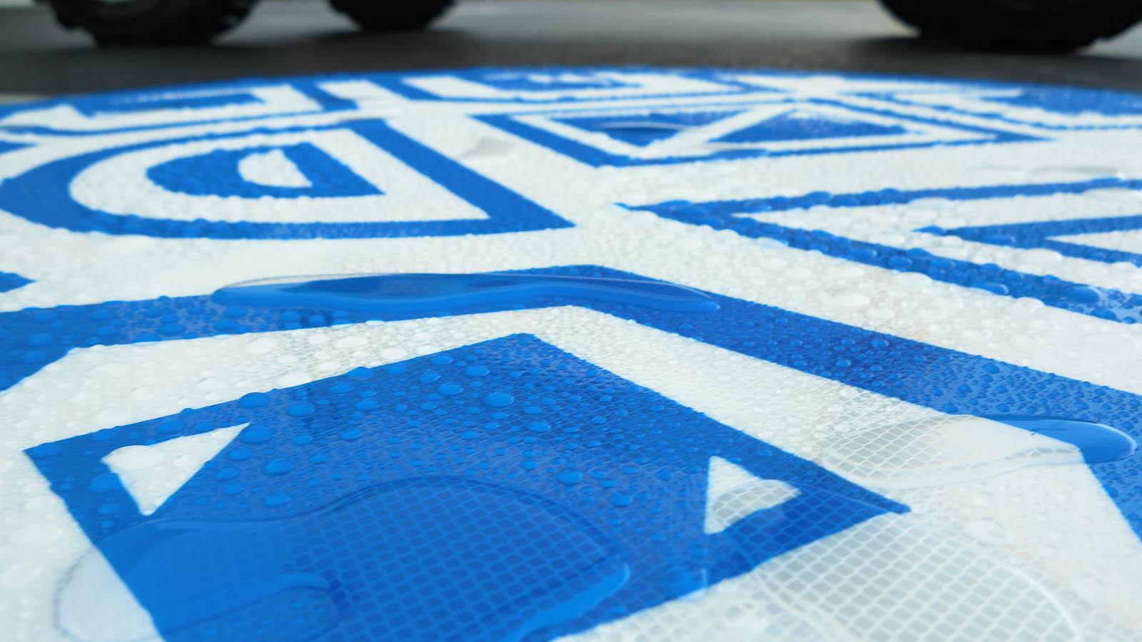 Detalj av regnvåt, blåvit skylt i reflexlaminat. Anton Wiraeus, Vägledare