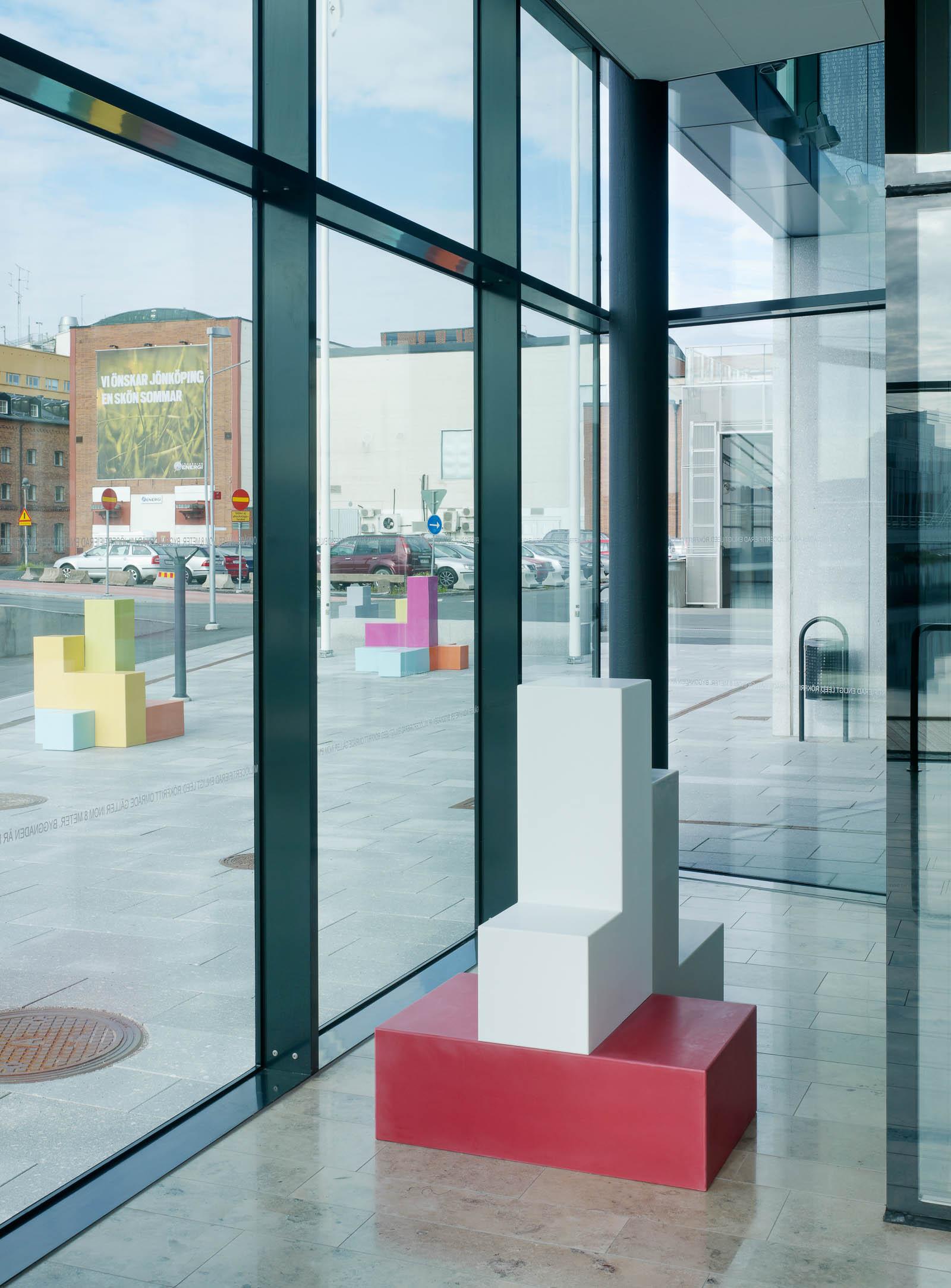 Skulptur med ett rött, ett vitt och ett grått block. I bakgrunden glasfasad mot gatan och flerfärgade skulpturer utanför. Jacob Dahlgren, Tetris, 2012.