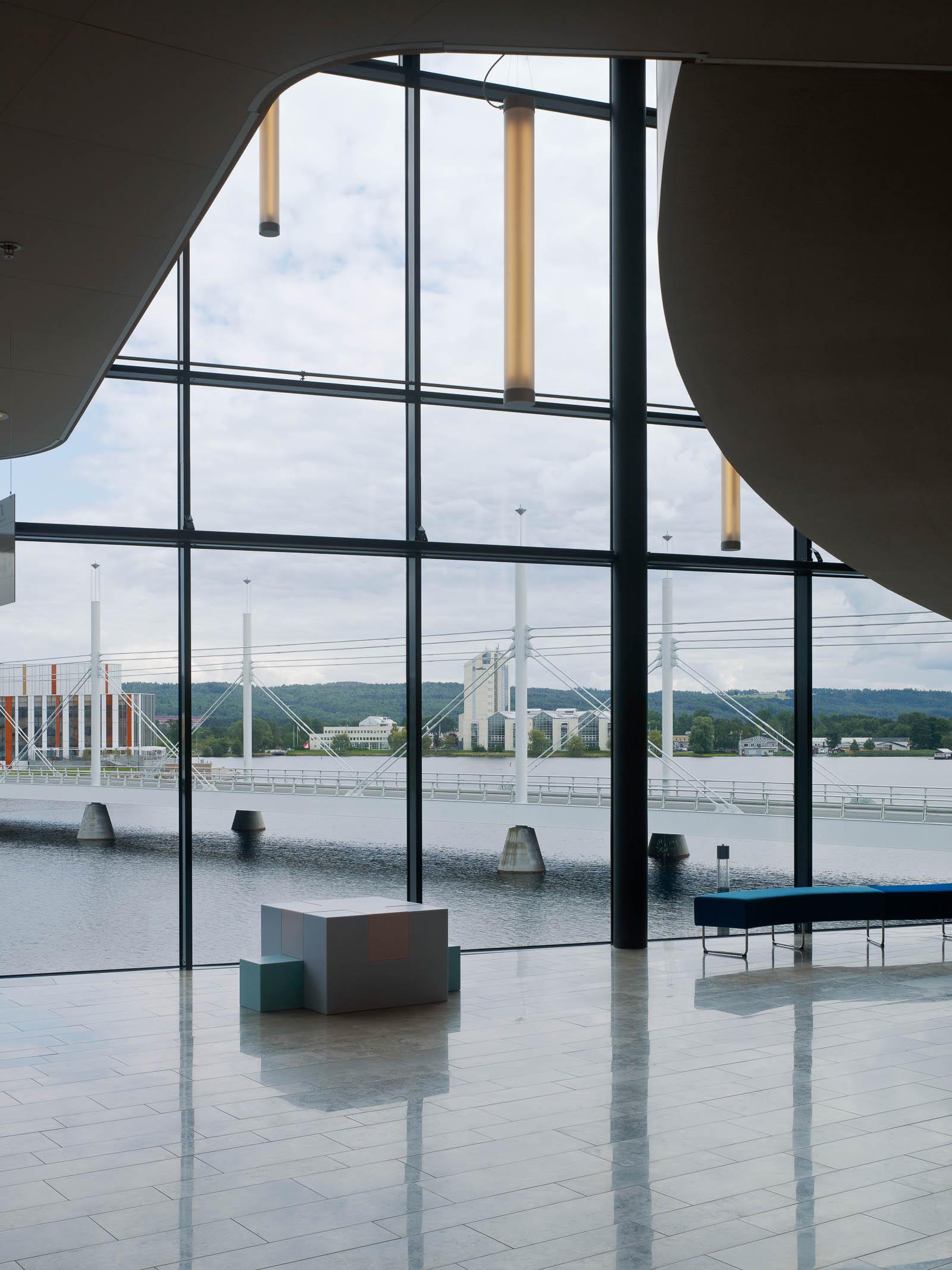 Inifrån byggnaden genom glasfasaden syns vattnet och en lång järnbro. Innanför fönstret en vit och blå skulptur. Jacob Dahlgren, Tetris, 2012.