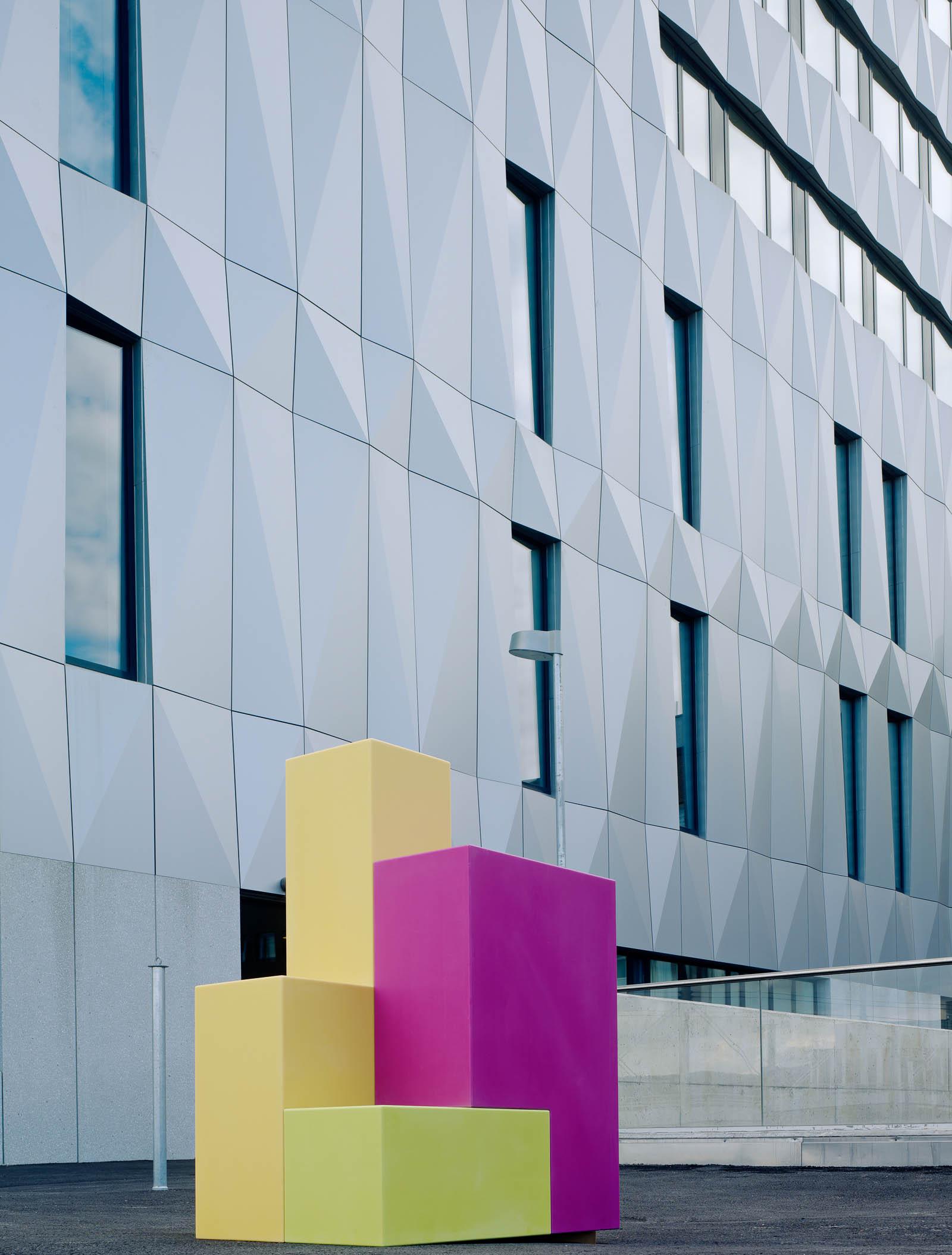 Skulptur utomhus med rosa och gula rätblock på högkant och ett litet grönt block vid foten. Jacob Dahlgren, Tetris, 2012.