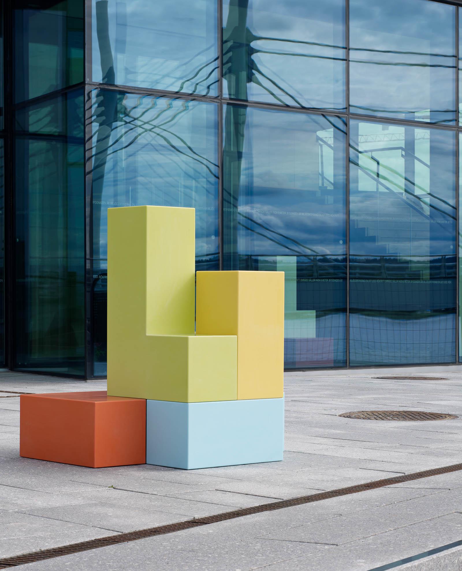 Skulptur utomhus. Ett blått och ett orange block i basen och ett gult och ett grönt block placerade ovanpå. Jacob Dahlgren, Tetris, 2012.