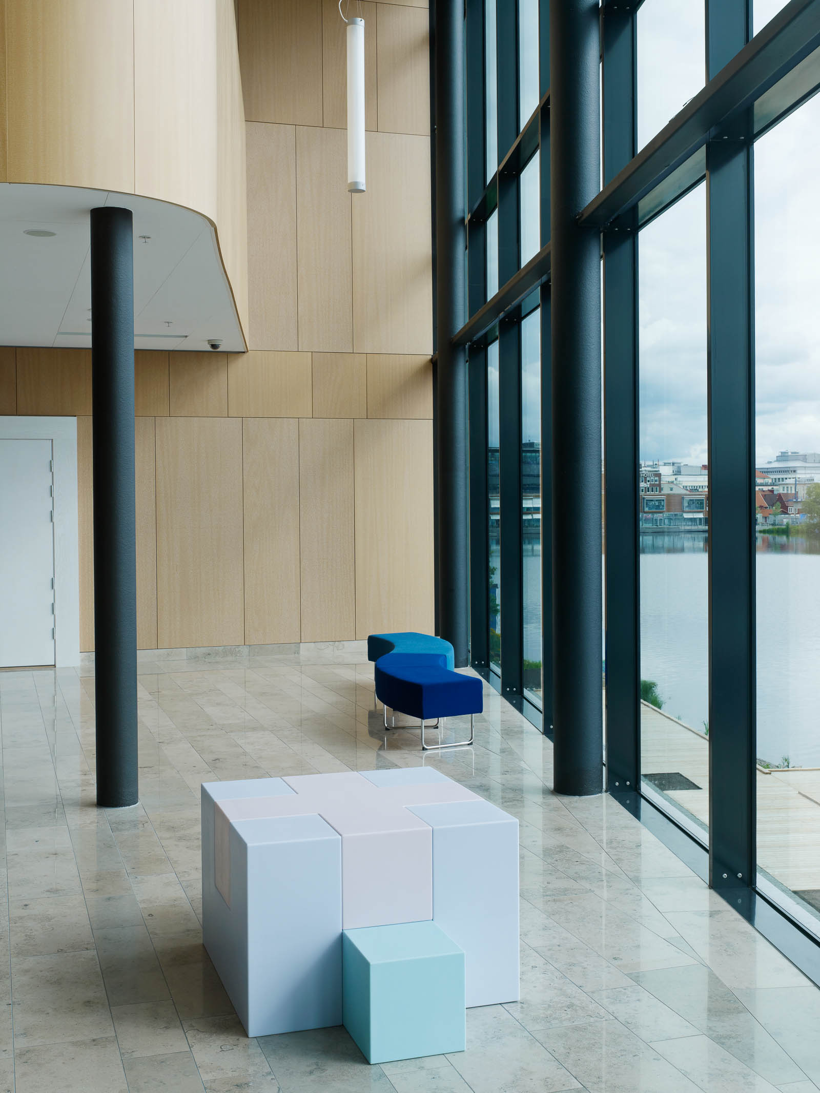 Skulptur bestående av en stor vit och en liten blå kub, vid en sittbänk nära glasfasad ut mot vattnet. Jacob Dahlgren, Tetris, 2012.