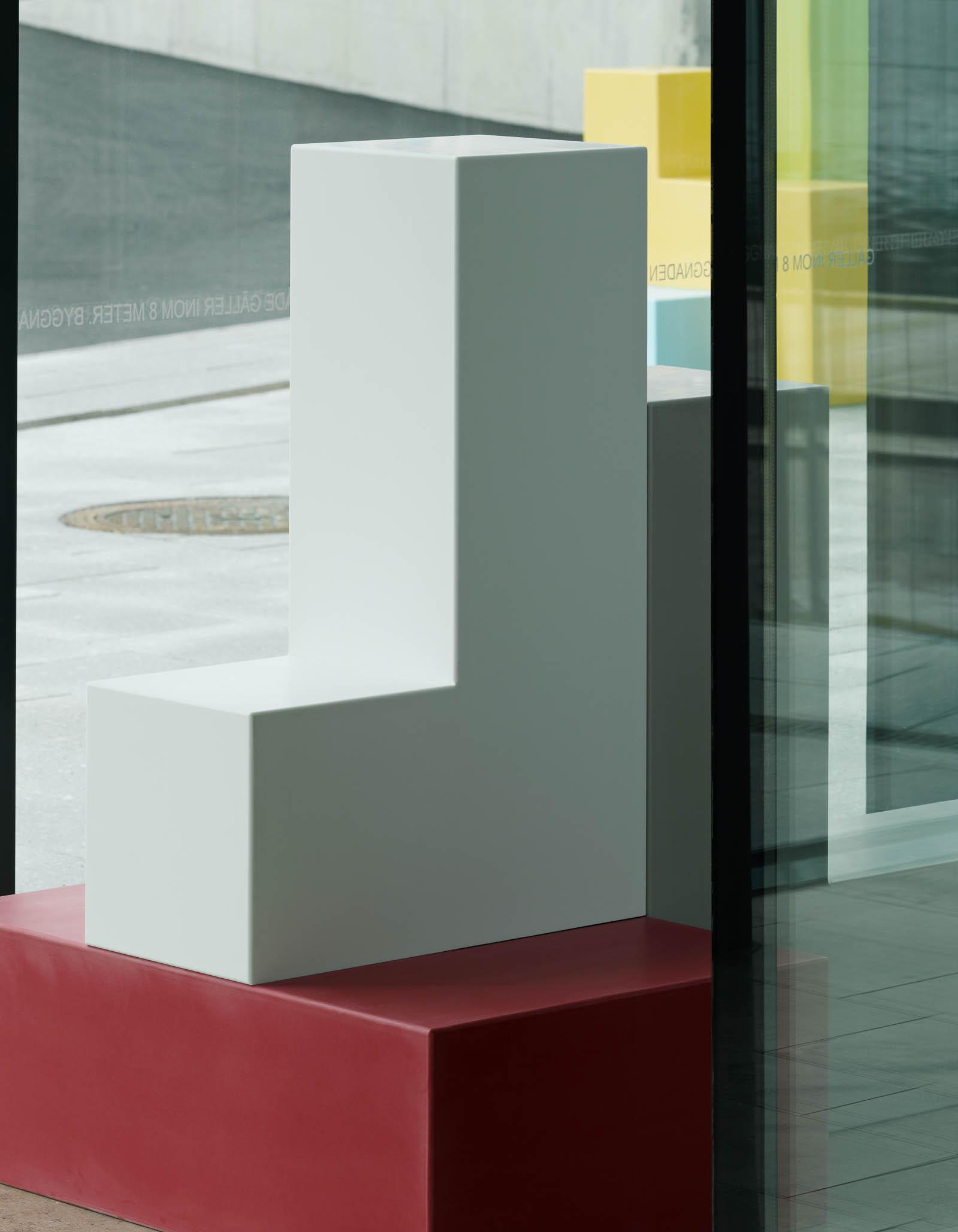 Skulptur inomhus bestående av ett rött rätblock i basen och två L-formade block i vitt och grått placerade ovanpå. Jacob Dahlgren, Tetris, 2012.