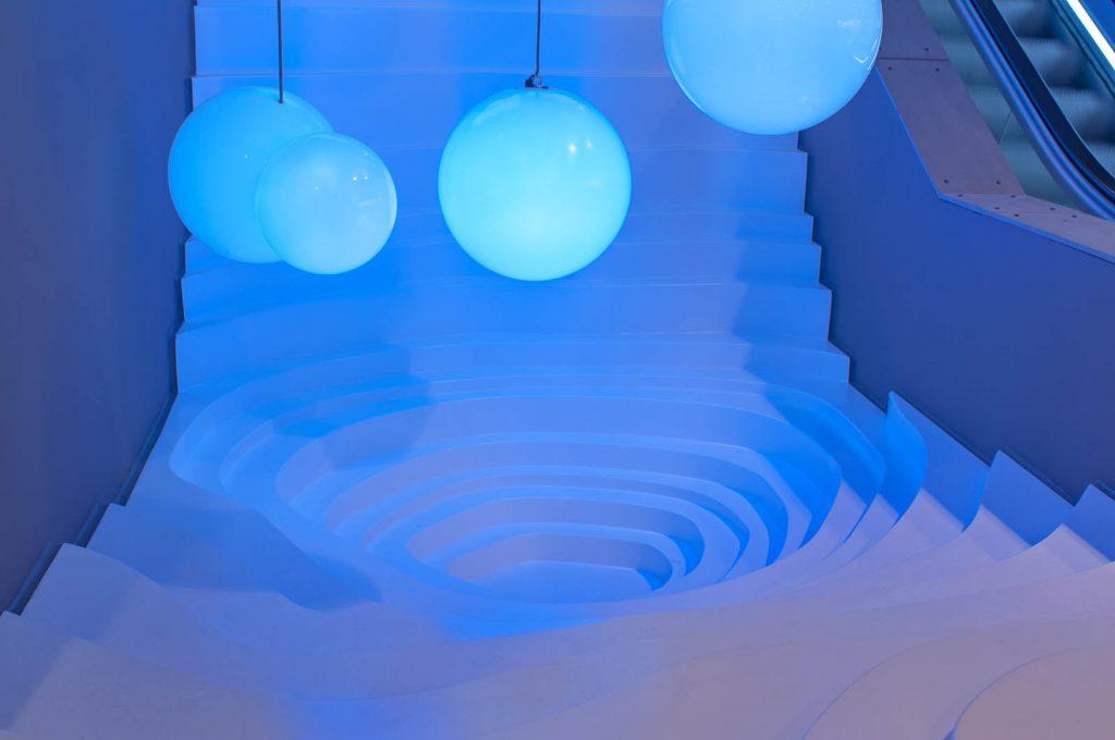 Under de nedersta blå lamporna något som liknar en cirkulär vit trappa med ojämna trappsteg som slutar i en nedsänkning. Bigert & Bergström, Morgondagens Väder, 2012