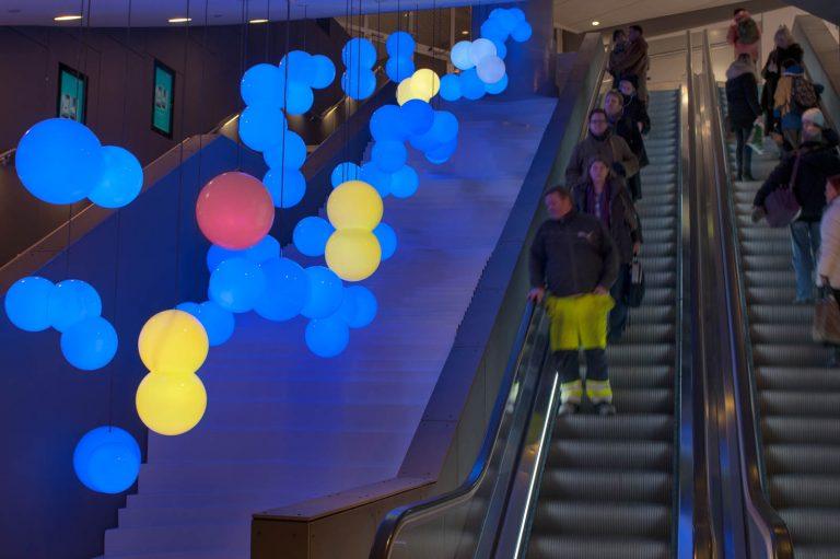 På ena sidan människor som åker rulltrappa. I taket på andra sidan hänger mängder av lampor i blått, gult och rött ovanför något som liknar en ojämn vit trappa. Bigert & Bergström, Morgondagens Väder, 2012.