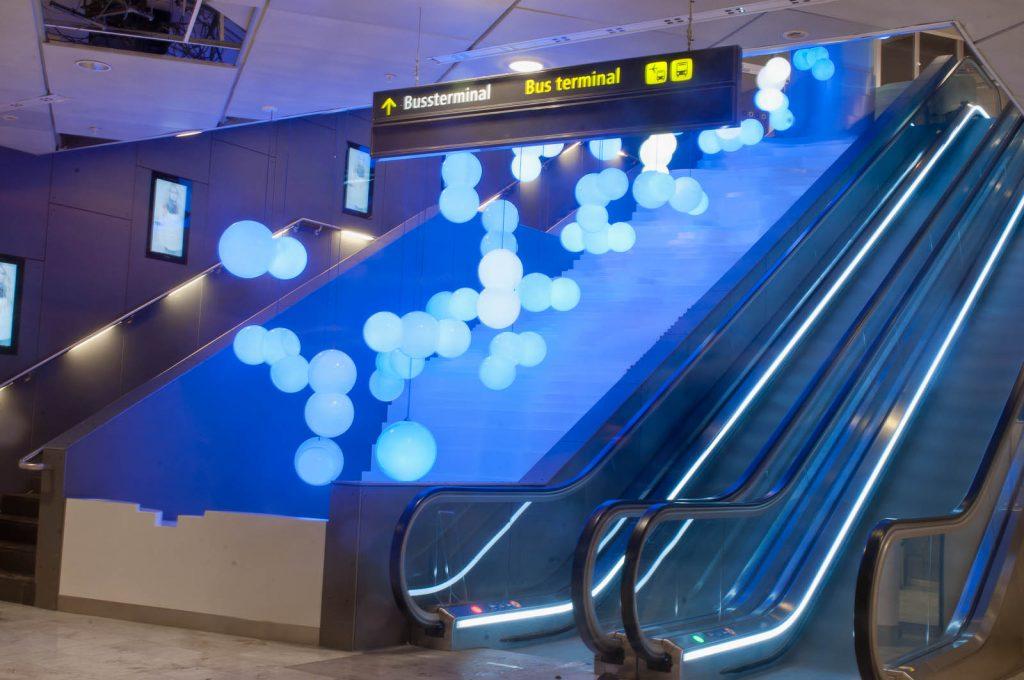 En mängd klotrunda lampor i olika nyanser av blått, hänger bredvid en rulltrappa. Ovanför skyltat mot bussterminal. Bigert & Bergström, Morgondagens Väder, 2012