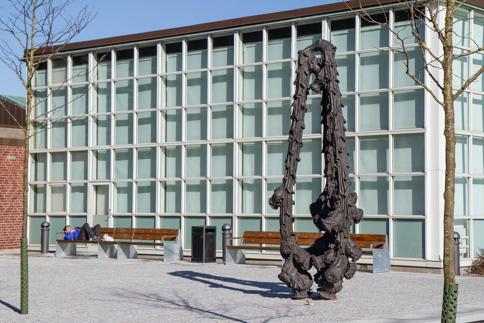 Hög bronsskulptur. I bakgrunden bänkar och en byggnad. Carl Boutard, Into The Wild (2013)