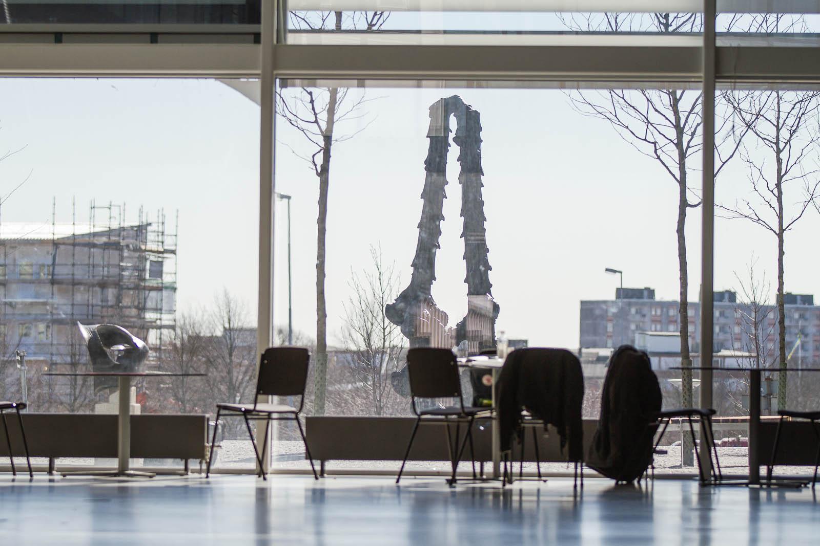 Bord och stolar framför en glasvägg. Utanför en hög tudelad och en lägre bronsskulptur. Carl Boutard, Into The Wild (2013)