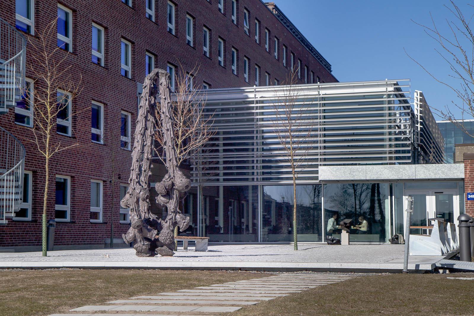 Bronsskulptur utanför tegelbyggnad. Dess tre armar påminner om grenar som möts i toppen. Carl Boutard, Into The Wild (2013)