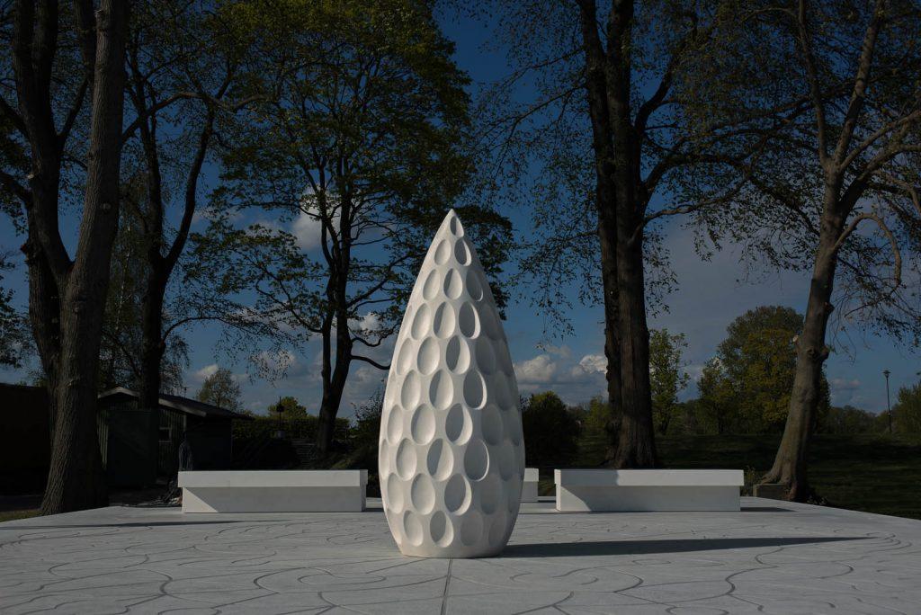 En hög vit stenskulptur, med formen av ett utdraget ägg. Skulpturen står på ett vitt stengolv, med vita bänkar bredvid sig. Monika Larsen Dennis, Restare, 2013