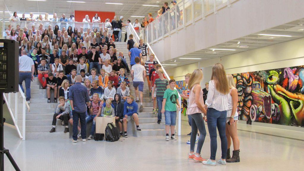 Nästan hela trappan är fylld av sittande ungdomar. Andra står i grupper eller rör sig upp mot balkongen på första våningen. Pärra Andreasson, Vad Vi Vill