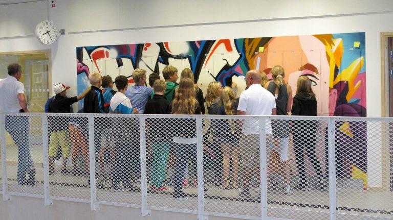 En stor grupp ungdomar trängs framför sina graffitimålade skåp, i färd med att låsa upp dem. Pärra Andreasson, Vad Vi Vill.
