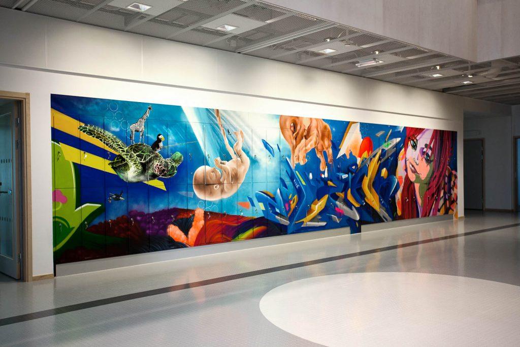 Blågrundad väggmålning med bl.a. ett kvinnoansikte, ett foster och en sköldpadda med en zebra på ryggen. Pärra Andreasson, Vad Vi Vill, 2013