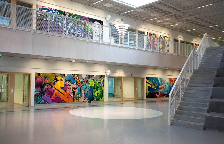 Från ingångshallen syns ett flertal målningar längs väggarna på båda våningsplanen. Pärra Andreasson, Vad Vi Vill, 2013