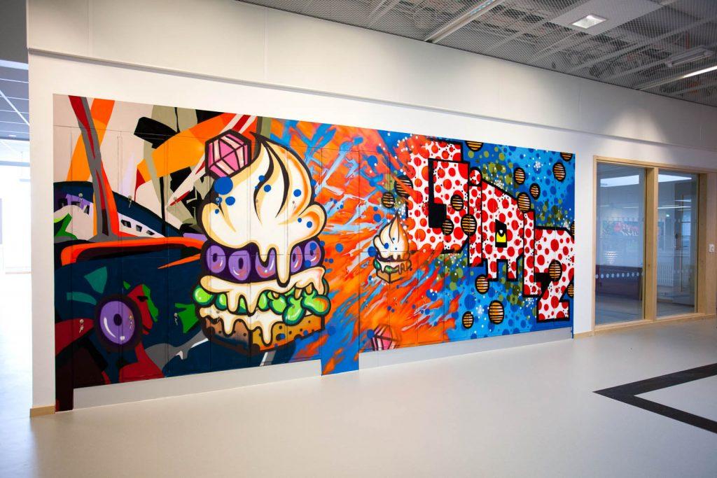 Väggmålning med två brinnande hamburgare och en exploderande text. Pärra Andreasson, Vad Vi Vill, 2013