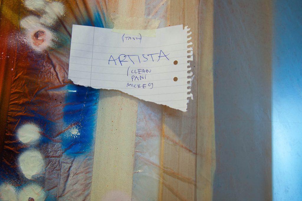 Färgfläckig byggplast med en upptejpad lapp om att ta bort färgen. Pärra Andreasson, Vad Vi Vill
