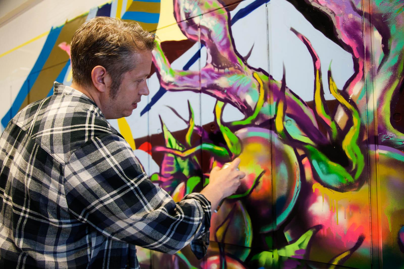 En man i färd med att spraya på en väggmålning. Pärra Andreasson, Vad Vi Vill