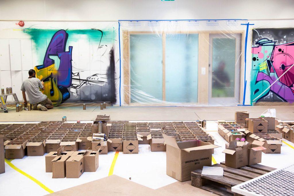 En man sitter på golvet i färd med att göra en graffitimålning. Väggen bredvid är täckt av plast. Bakom honom mängder av pappkartonger. Pärra Andreasson, Vad Vi Vill