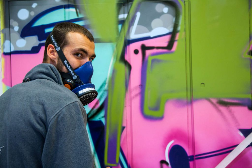 En man med gasmask framför en graffitimålning. Pärra Andreasson, Vad Vi Vill
