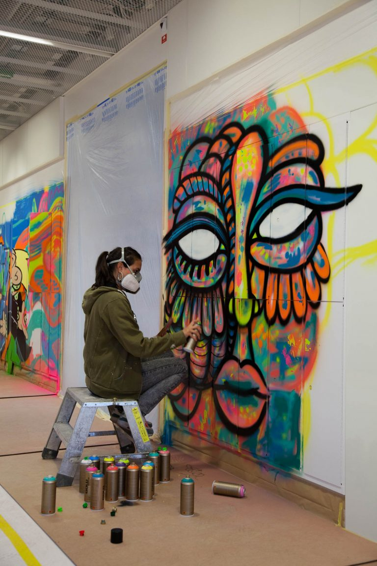 Kvinna med munskydd sitter på en pall och sprejar en graffitimålning av en färgglad fågelkvinna på väggen. På golvet sprayburkar. Pärra Andreasson, Vad Vi Vill, 2013