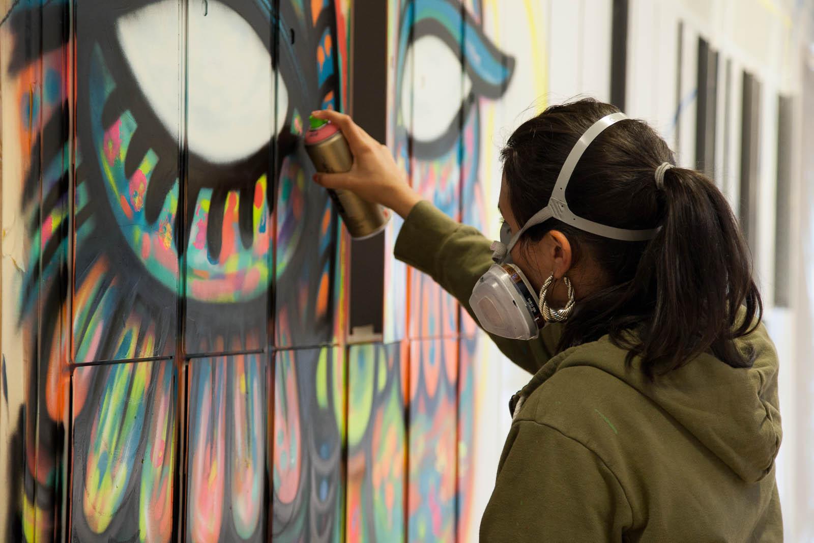 En kvinna i gasmask sprayar en färgglad fågelkvinnas ansikte på väggen. Pärra Andreasson, Vad Vi Vill