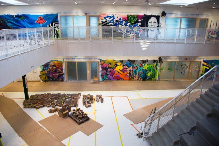 Dörrarna i ingångshallen är täckta med byggplast och golven med papp. I mitten ligger mängder av små pappkartonger. På skåpen mångfärgade graffitimålningar. Pärra Andreasson, Vad Vi Vill