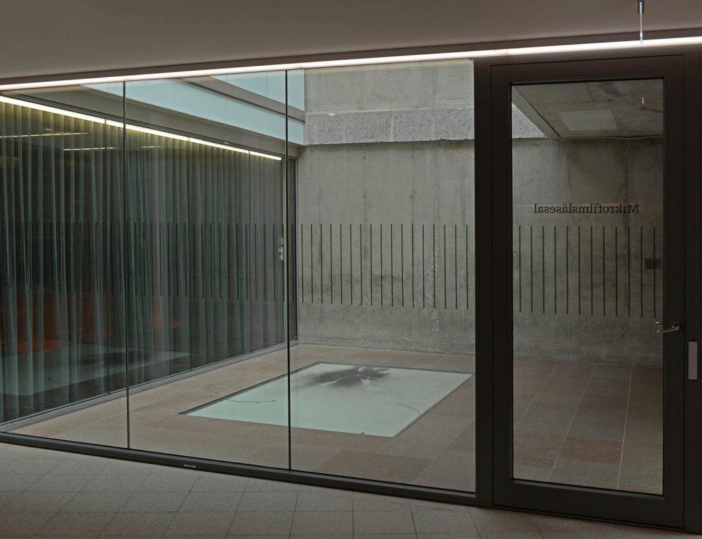 I ett utrymme med glasväggar och stengolv ligger en glasplatta med utspritt kolpulver. I kolets svärta syns de vita spåren av elektricitetens framfart. Nina Canell, Impulse Slight (100 000 Volt)