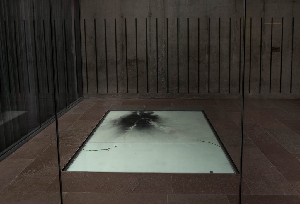 Den vita golvplattan med kol och två elsladdar. Nina Canell, Impulse Slight (100 000 Volt)
