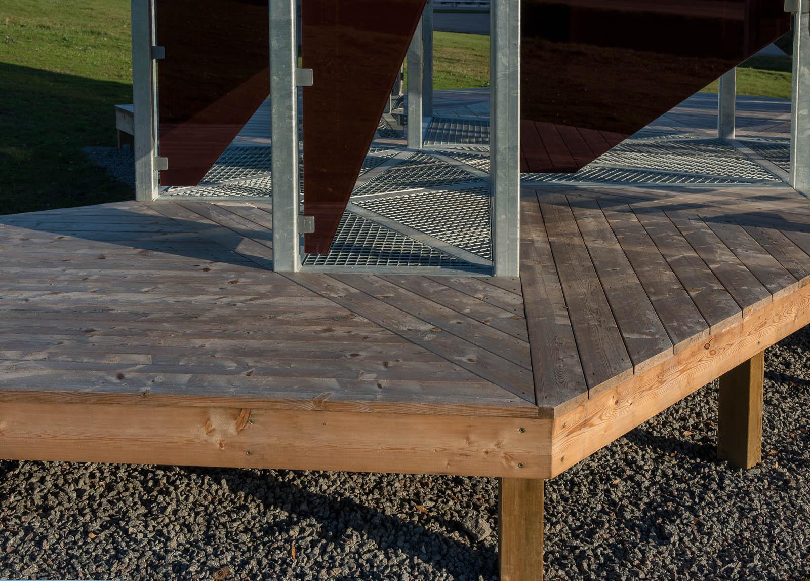 Verkets bas är ett upphöjt trägolv på grus i vilket metallstängerna med glasskivor är fästa. Patrik Aarnivaara, Tidsglänta, 2013.