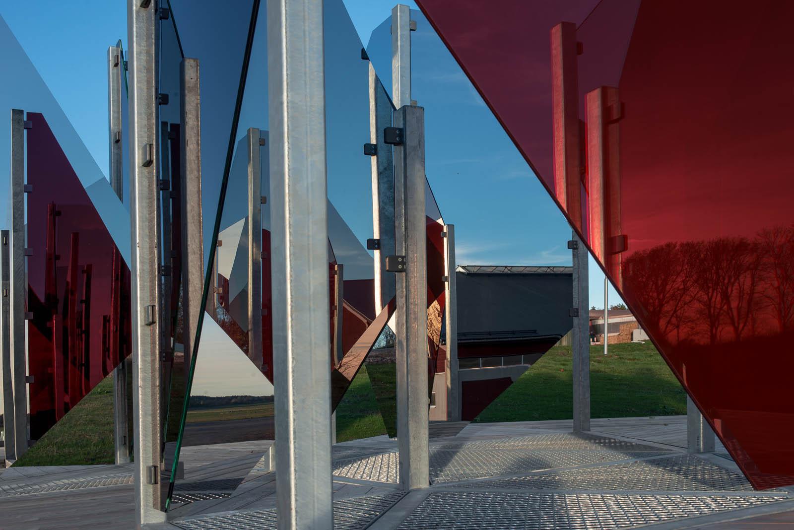 Del av verket. Röda och vita glasskivor fästa på metallstänger. Patrik Aarnivaara, Tidsglänta, 2013.