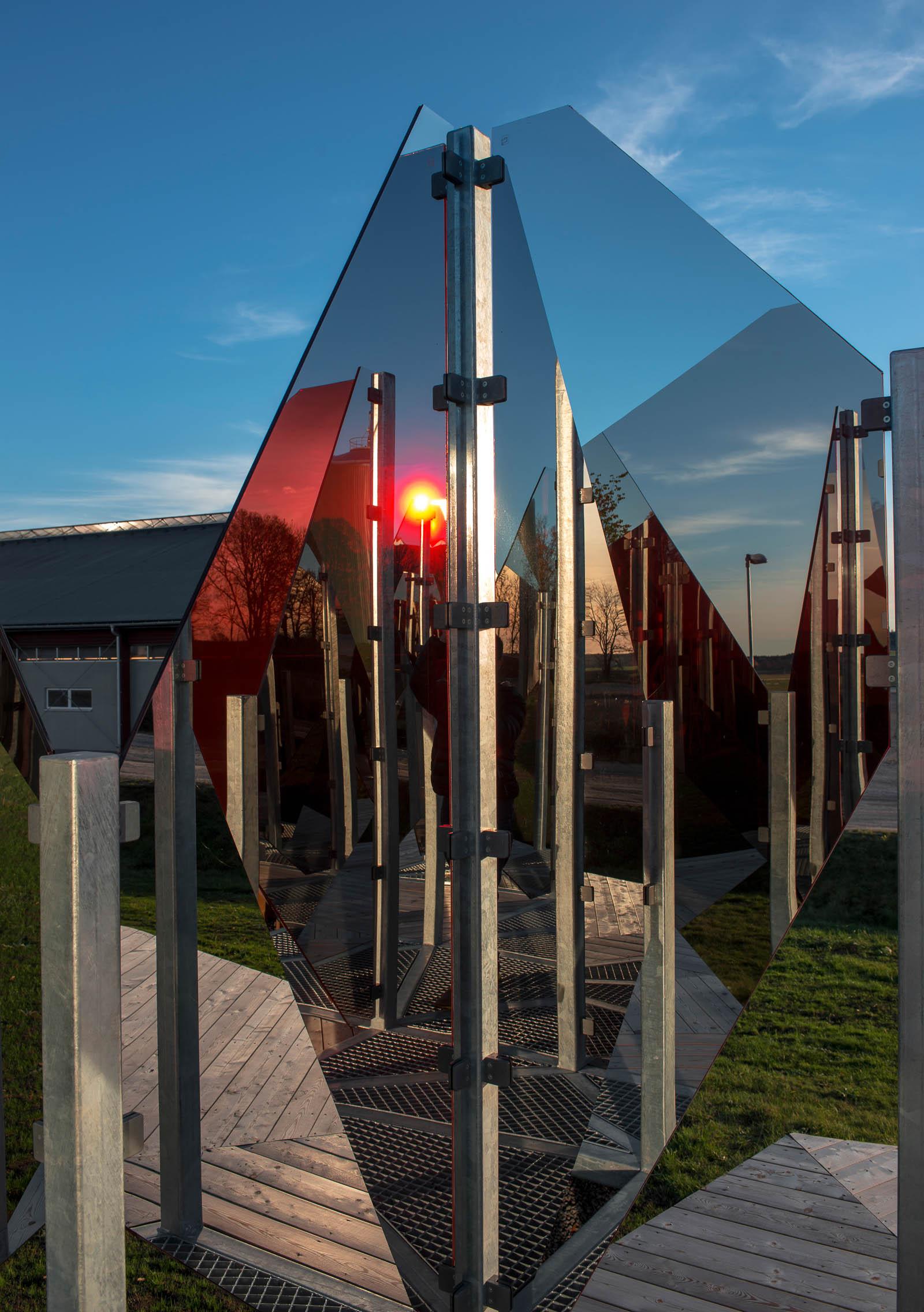 På nära håll skapas en mosaik av speglingar från olika håll. Även den sjunkande solen fångas av glaset. Patrik Aarnivaara, Tidsglänta, 2013.