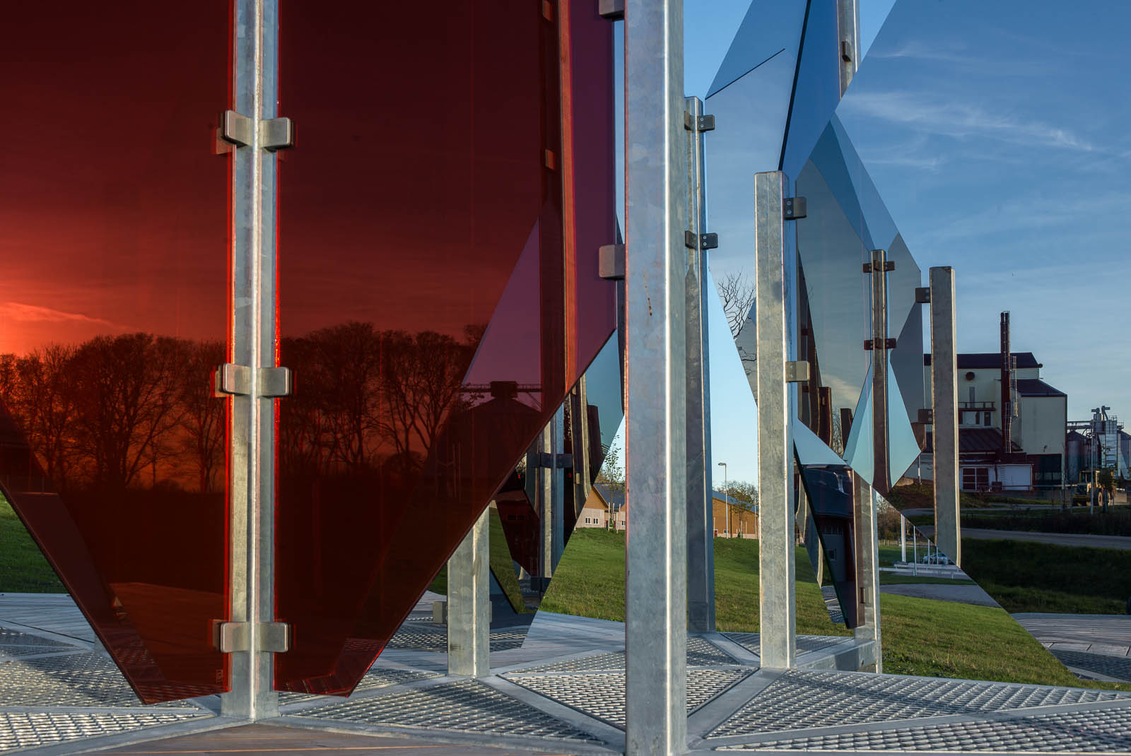 I de röda och vita triangulära glasskivorna reflekteras träd och en byggnad med stor skorsten. Patrik Aarnivaara, Tidsglänta, 2013.
