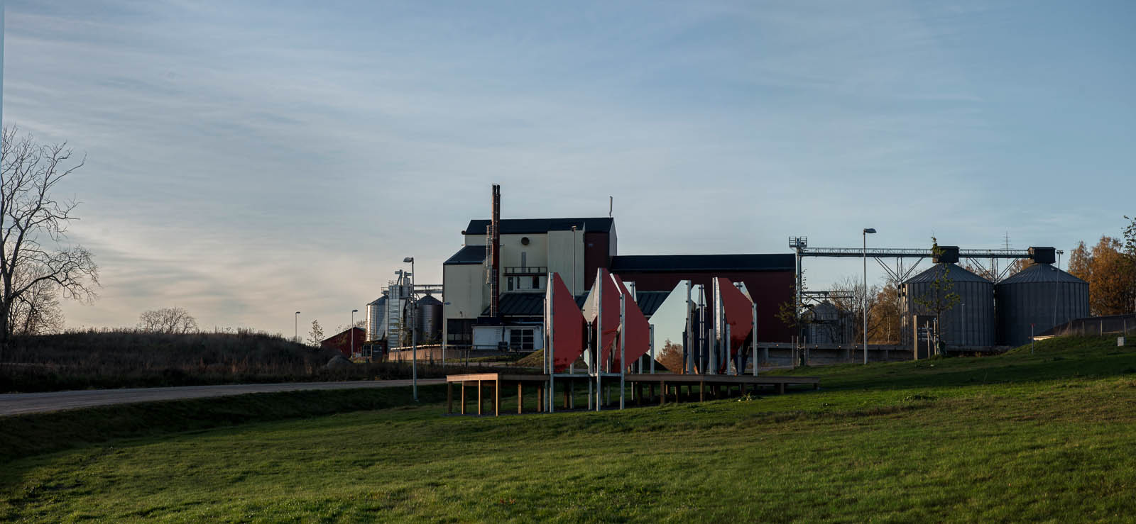Verket står på en gräsmatta. I bakgrunden biogasanläggningen med skorsten och grå cisterner. Patrik Aarnivaara, Tidsglänta, 2013.