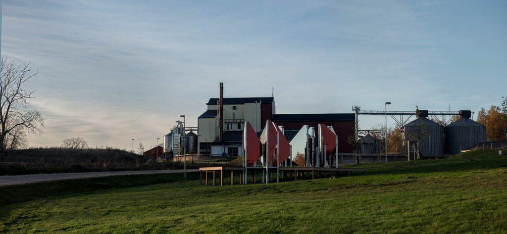 Verket står på en gräsmatta. I bakgrunden biogasanläggningen med skorsten och grå cisterner. Patrik Aarnivaara, Tidsglänta, 2013