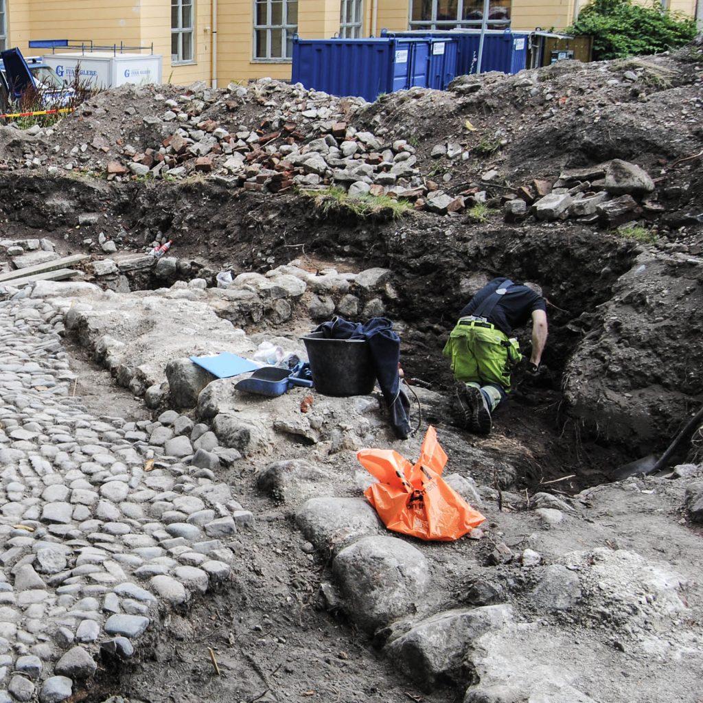 Pågående utgrävning. En man ligger på knä och gräver i jorden bredvid gamla kullerstenar och något som skulle kunna vara en husgrund. Kvarteret Valnötsträdet, utgrävningar 2013