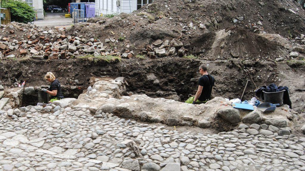 En kvinna och en man i arbetskläder står upp till midjan i varsitt hål och arbetar med utgrävningen. Vid sidan jordmassor och uppkastade stenar. Kvarteret Valnötsträdet, utgrävningar 2013