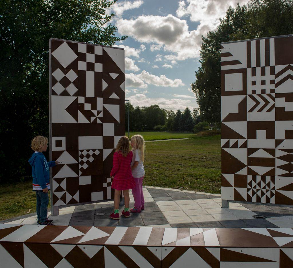 Barn vid höga skärmar med geometriska mönster i vitt och brunt. I bakgrunden gräs och träd. Folkform, Vanstaskolan i Nynäshamn, 2013