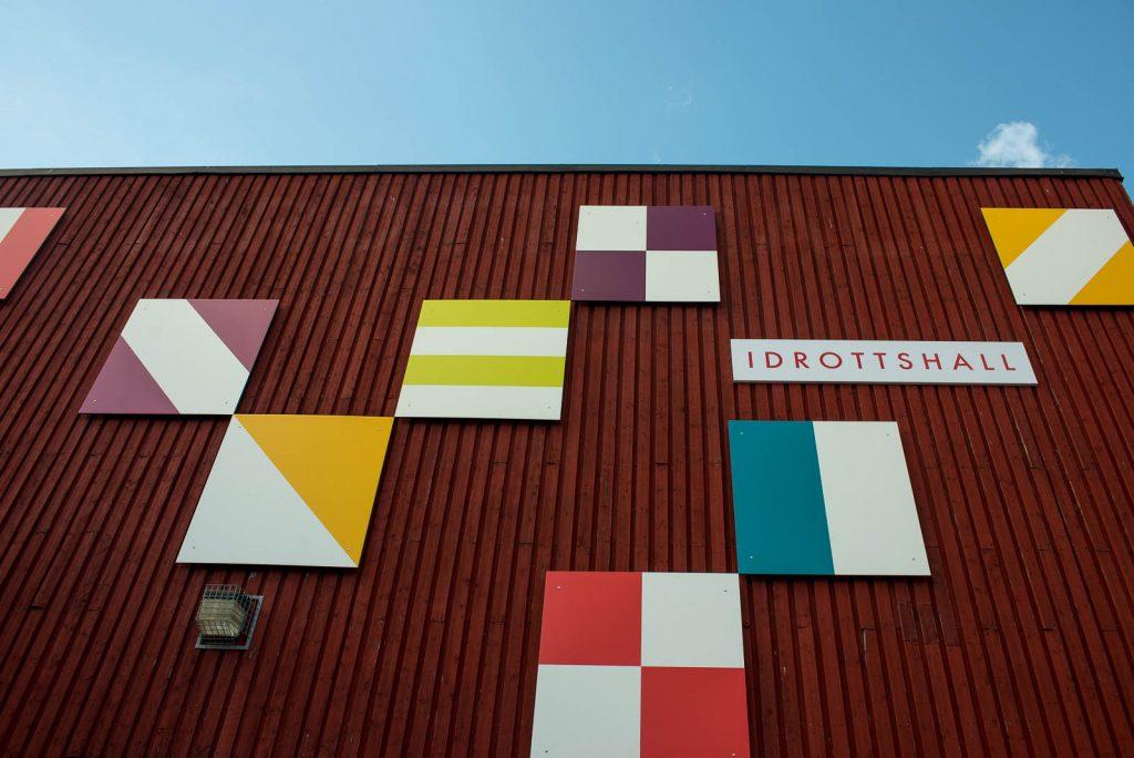 """Idrottshallens röda träfasad med de färgade fyrkantiga """"flaggorna"""". Folkform, Vanstaskolan i Nynäshamn, 2013"""
