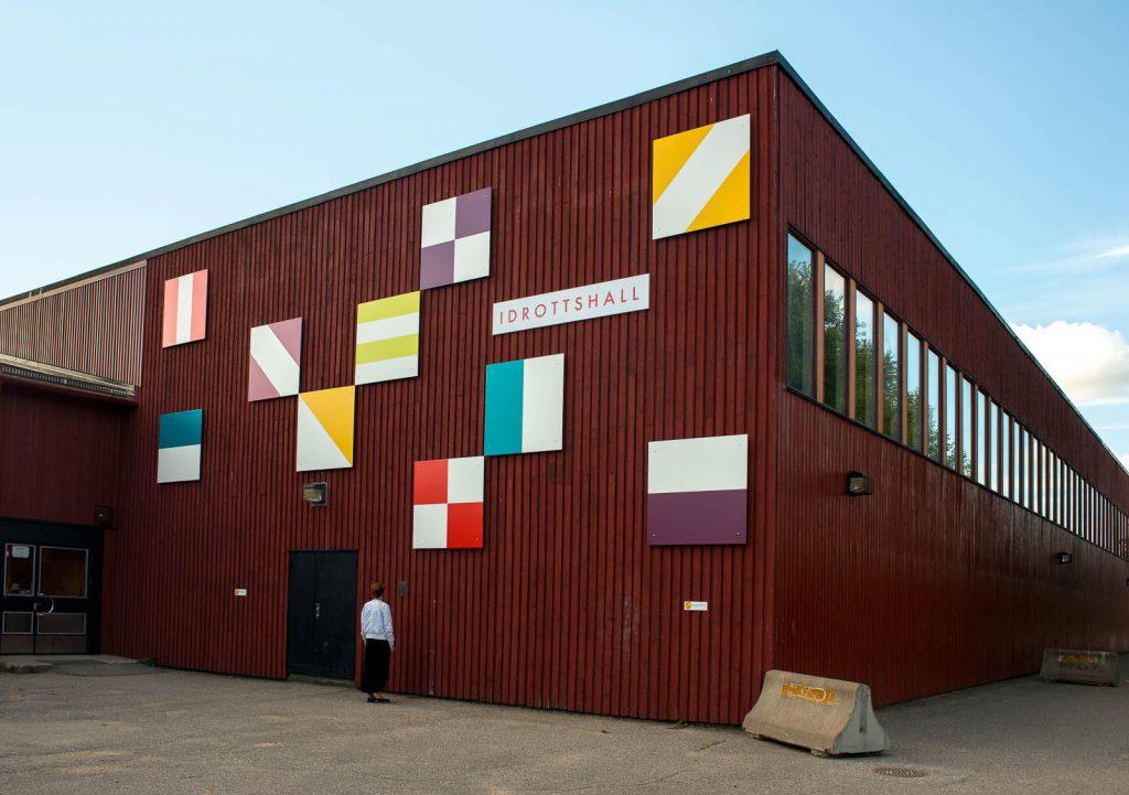Röd idrottshall med mönstrade fyrkanter i olika färger på fasaden. Folkform, Vanstaskolan i Nynäshamn, 2013