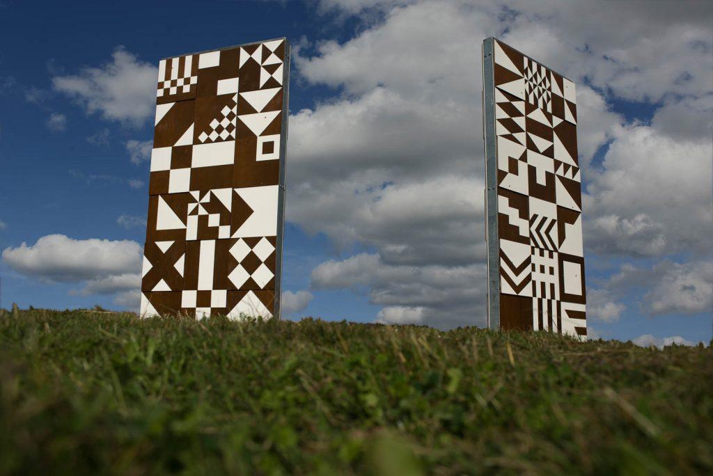 Två höga skärmar med geometriska mönster i vitt och brunt, fotograferade med himlen som fond. Folkform, Vanstaskolan i Nynäshamn, 2013