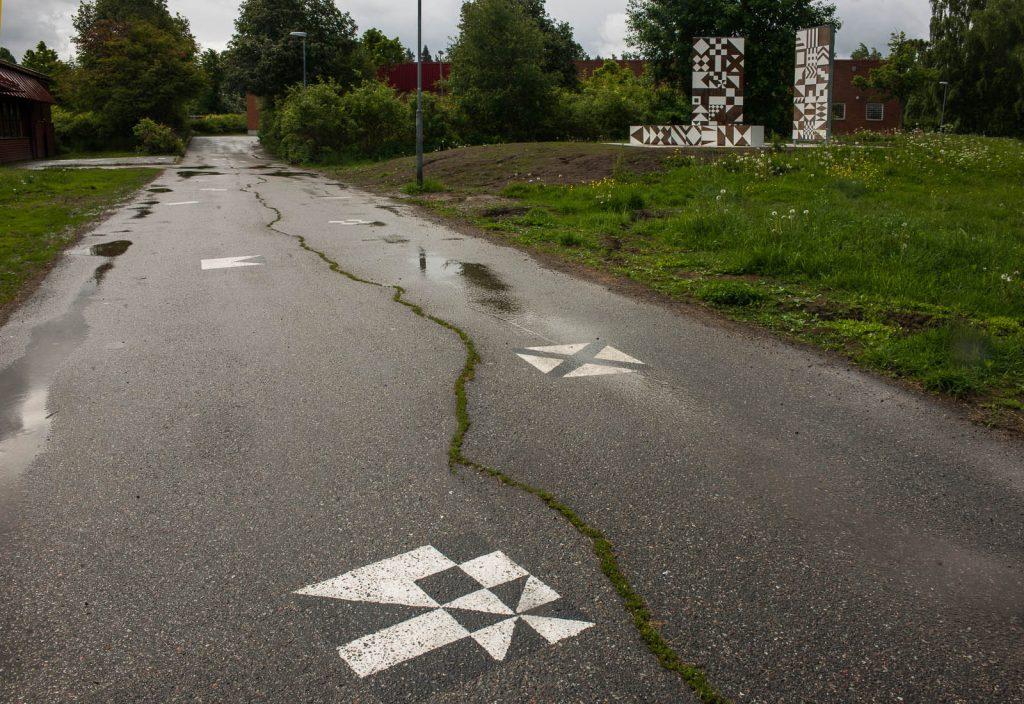 Geometriska mönster i vitt på asfaltsväg. I bakgrunden bruna skärmar med samma vita mönster. Folkform, Vanstaskolan i Nynäshamn, 2013