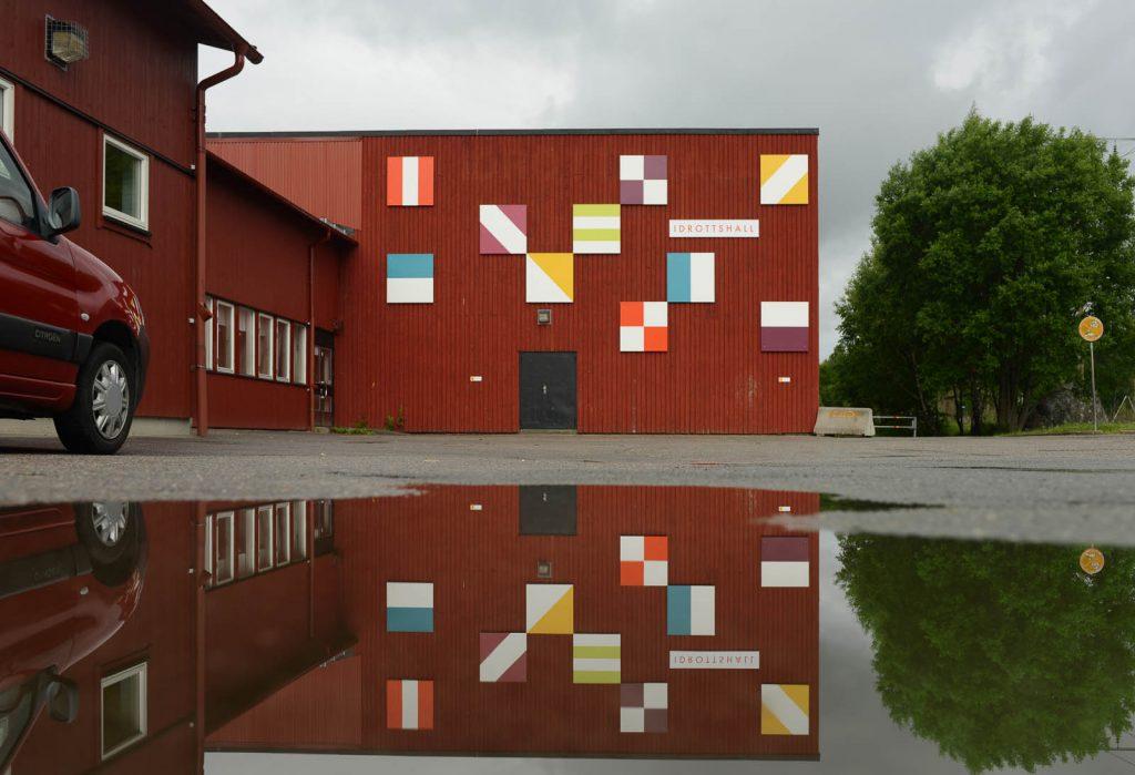 Röd idrottshall med tio mönstrade fyrkanter i olika färger på fasaden. Folkform, Vanstaskolan i Nynäshamn, 2013