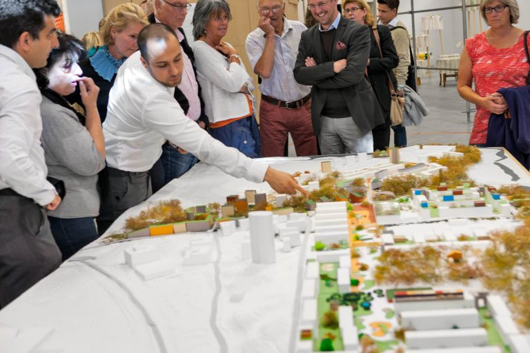 Människor står samlade runt en områdesmodell. Någon pekar och diskuterar. Parklek på Marabouparken, 2012