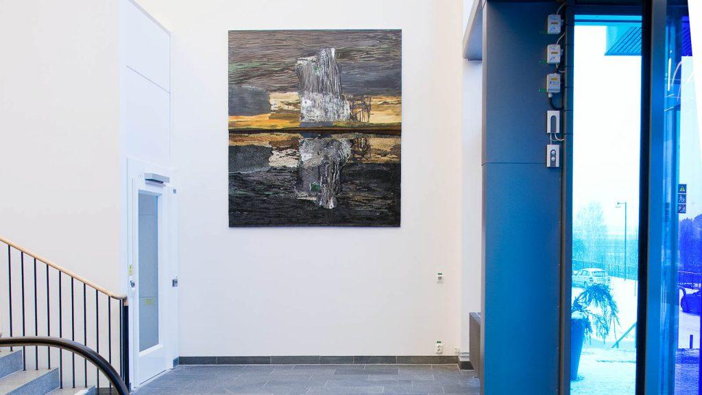 Verket hänger i entréhall mellan ingångsdörr och hiss. Tudelat verk. Överdelen är ett målat landskap, nederdelen är en textil invertering av landskapet, på håll ser det ut som en vattenspegling. Andreas Eriksson, Natt som dag, 2013