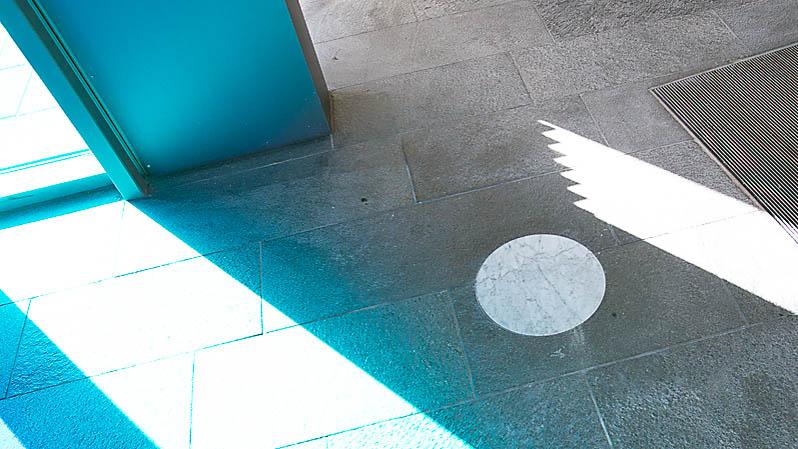 Direkt innanför dörrarna är en liten cirkel inlagd i golvet. Den ljusa kolmårdsmarmorns runda form avtecknar sig distinkt mot den mörkare skifferstenen runt omkring. Andreas Eriksson, Natt som dag, 2013