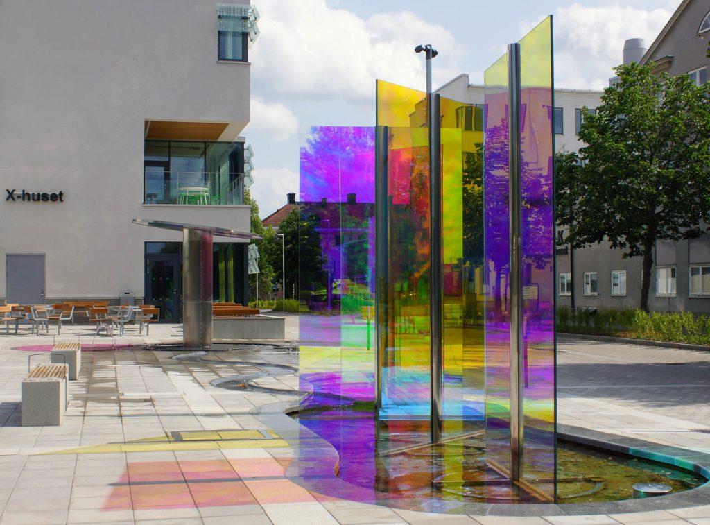 Glasskivor i en fontän, som skiftar i ett spektrum mellan lila, rosa, gult och grönt. Torbjörn Johansson, Källan Är, 2014