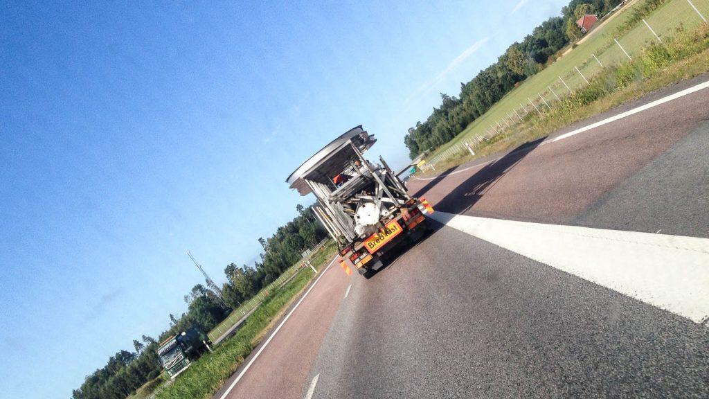 Transport med alla rostfria delar. Lastbil på motorväg.