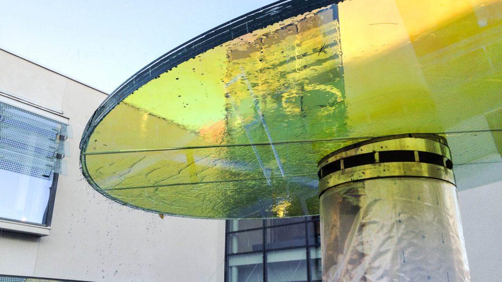 Det runda glaset över fontänen och seglen är laminerat med en folie som reflekterar, speglar och bryter ljus. Fontänens/källans glastak ser gult ut på bilden. Torbjörn Johansson, Källan Är