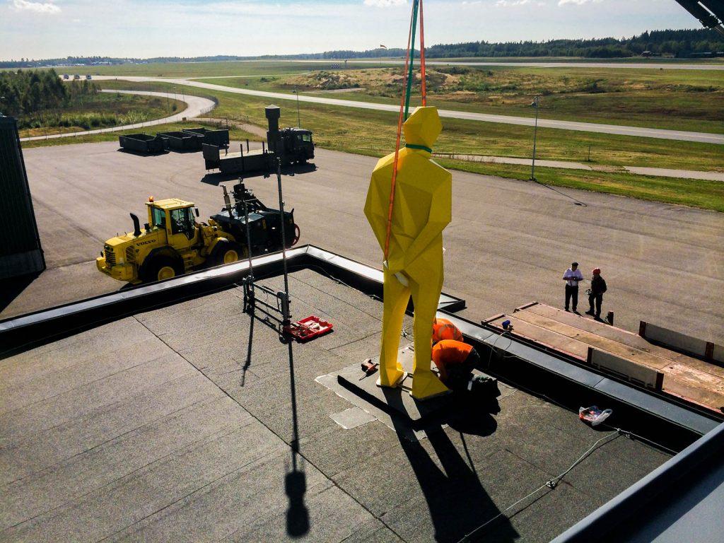 Skulpturen hissas ner på taket med remmar. Xavier Veilhan, Julian, 2014.