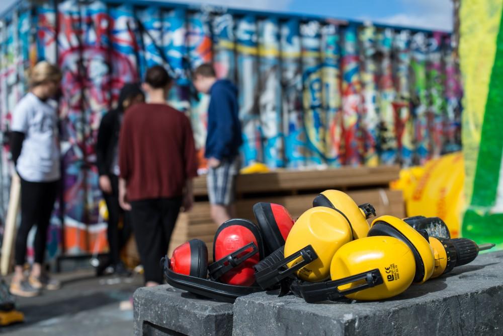 I förgrunden röda och gula öronkåpor. Bakom kåporna en grupp människor vid en trave med byggmaterial. Santiago Cirugeda & Loulou Cherinet, How/Gibca